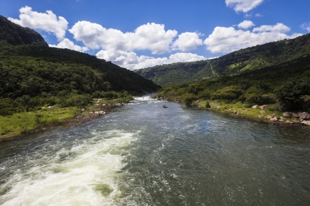 swiftly: River waters flowing swiftly down through the rural green tall valley