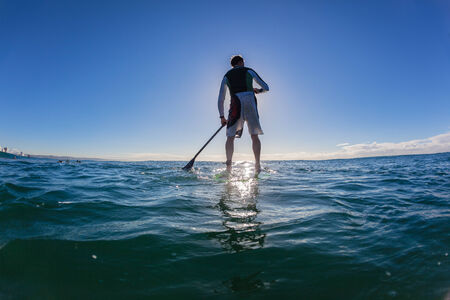 Surfing sup surfers standing on surfboards with paddles in morning ocean waiting to ride waves Stock Photo