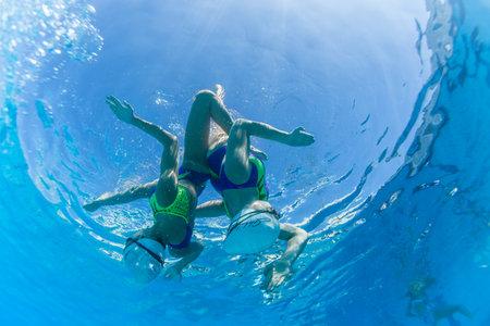 nataci�n sincronizada: Acu�tico sincronizado pares de las muchachas que bailan programas superficie bajo el agua en el Nationals campeonatos
