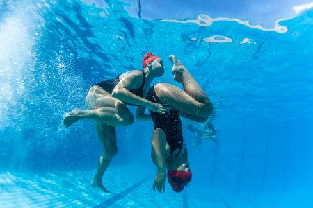 Aquatische Kunstzwemmen meisjes paren dansen onderwater oppervlak programma's op onderdanen kampioenschappen Stockfoto - 24738102