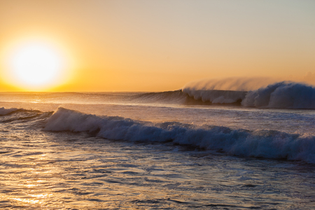 swells: Morning sunrise with large ocean wave swells pounding crashing sea water into reef shallows