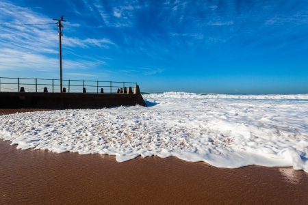 Ocean wave swells crashing washing sea water around beach sands and concrete beach tidal pool photo