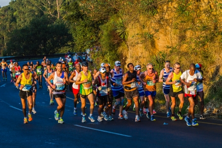 Marathon ultra distance race with groups of runners up long winding hill in morning sun light