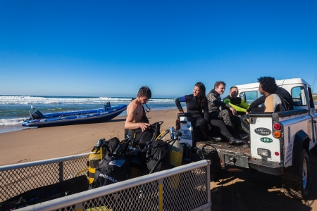 regulators: Scuba divers finished diving for the day sitting in 4x4 vehicle with bottle rigs in trailer leaving the beach Editorial