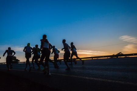 silhoutted: Marathon ultra race with groups of runners up long winding hill silhouetted in morning sun light