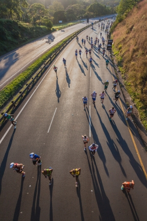 Marathon ultra race with groups of runners shadows up long winding hill  in morning sun light