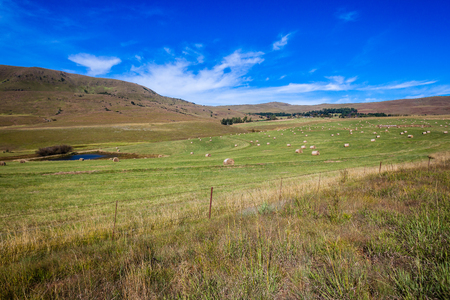 Rural mountains countryside landscape with grass cattle feed bales scattered  photo