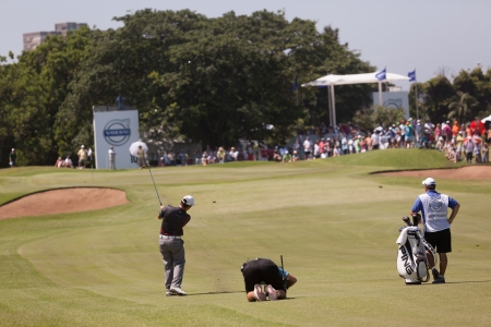 country club: Professional Golfer Louis Oosthuizen and tv camera swings to strike ball at European PGA Tournament Volvo Golf Champions Tournament play action at Durban Country Club  January 2014 South Africa Editorial