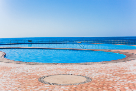 next horizon: Swimming pools outdoor next to ocean sea side with blue horizon