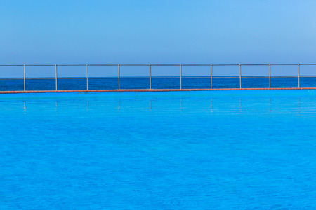 next horizon: Swimming pool outdoor next to ocean sea side with blue horizon