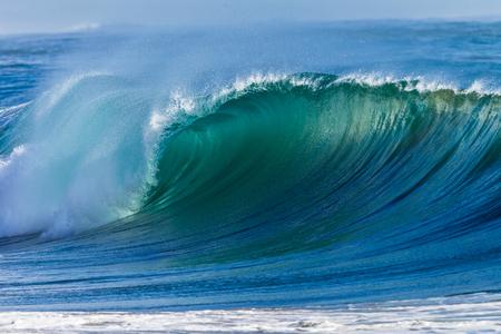 Oceaandeining golf beweegt crashen naar ondiep strand zandbanken Stockfoto