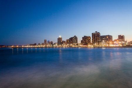 Durban strand verlichting en gebouwen in de schemering over zeewater