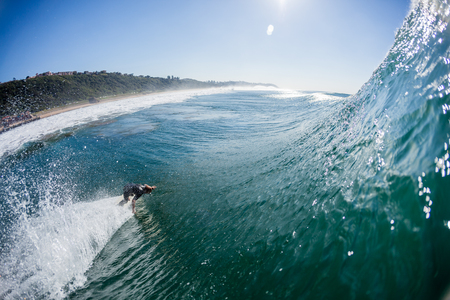 kz: Surfer rides off the bottom of vertical wall wave down the line,a water photo perspective
