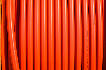Telecom orange colored plastic pipe for fiber optic it communications connections underground installations to internet networks photo