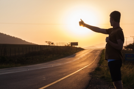 silhoutted: Male silhoutted by sun setting hitch hiking for a lift roadside