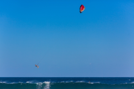 high winds: Surfing kite surfers launches high off  ocean wave riding swells with winds help propelling his kites