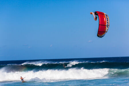 Surfing kite surfers in the ocean waves riding swells with winds help propelling their kites