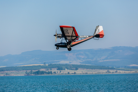 Microlight plane pilot flies low over dam waters landscape