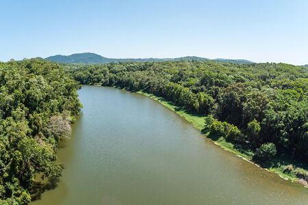 Wide river flows through tropical jungle forest with a birds eye view