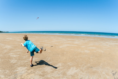Young boy throws boomerang over low tide sand tropical beach with calm blue sea ocean