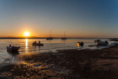 Fishermen in tinny boat home time sunset over smooth waters in estuary lagoon with silhouetted yachts photo