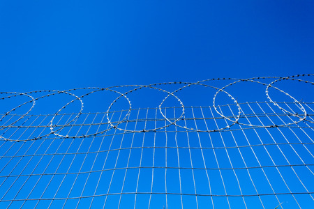 fencing wire: Razor wire attached to steel wire fencing to protect private property from intruders