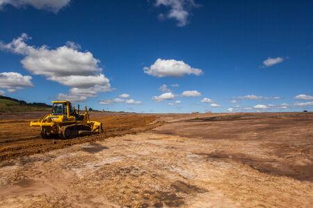 grading: Abriendo nuevos caminos, la conversi�n de tierras de cultivo para la construcci�n industrial de edificios de almac�n en un entorno rural con m�quinas de clasificaci�n de tierra sobre el suelo desnudo en el cielo azul paisaje