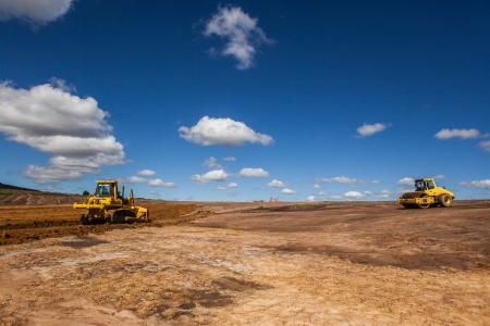 grading: Apertura de nuevos caminos, la conversi�n tierras de cultivo para la construcci�n industrial de edificios de almac�n en un entorno rural con m�quinas clasificadoras tierra sobre el suelo desnudo en el cielo azul paisaje Foto de archivo