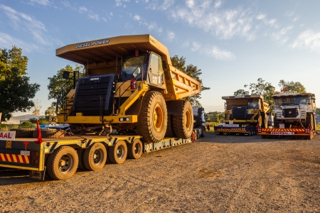 Large abnormal open cast mining heavy earth bucket truck vehicles on transport trailers to mining destination