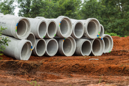 Concrete Round storm drain water pipes stacked for installation in civil construction road projects Stockfoto