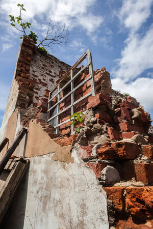 condemned: Condemned abandoned broken abandoned building wall with its roof collapsed gone with fallen walls and bricks in field yards  Demolishes in progress  Stock Photo