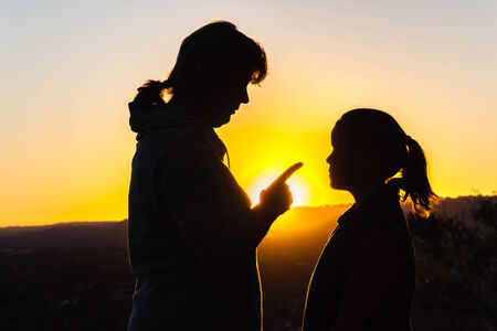 relationship love: Mother daughter affections relationship love discipline contrasts silhouetted in dusk sunset sky