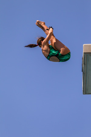 Girl in mid flight dive at national aquatic diving competition