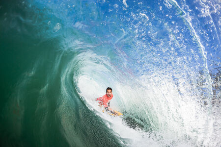 Body-Boarder surfing rides clean hollow tube crashing wave over shallow reef Swimming water perspective of sport  photo