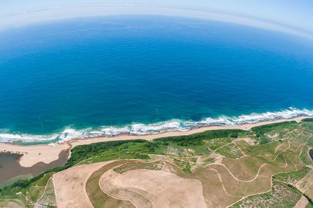 Air birds eye view blue ocean coastline sugarcane farming fields over the colorful landscape photo