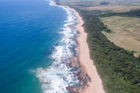Air birds eye view of Blue ocean rocky beach coastline bush trees fields over the colorful landscape photo