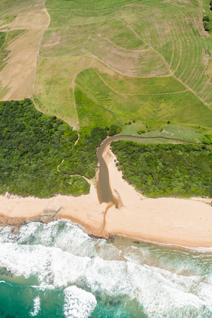 Air birds eye view of river beach sea waters sugarcane farming fields over the colorful landscape photo