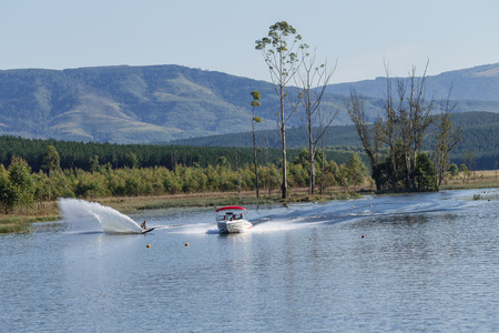 water skiers: Water-skiing event action of top local skiers at countryside lake dam in the rural forest terrain
