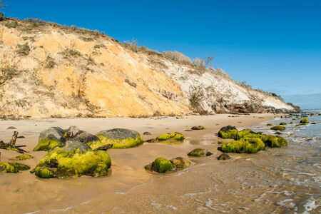 high winds: Natures beauty along beach rocks with high embankment of earth sand colors mixing blending by winds water weather climates along scenic beach coastline Stock Photo