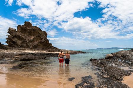 male and female: Beautiful beach ocean rocky heads blue water coastline landscape  Couple Male female swim in protected cove
