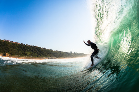 Surfer catching dropping riding surfing hollow crashing wave, a water swimming view of the action