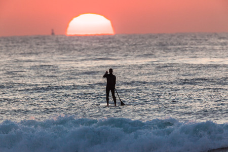 Sun Horizon Surfer paddles on SUP board on ocean waters at sunrise