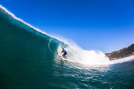 Surfer catching riding surfing large blue crashing wave, a water swimming view of the action