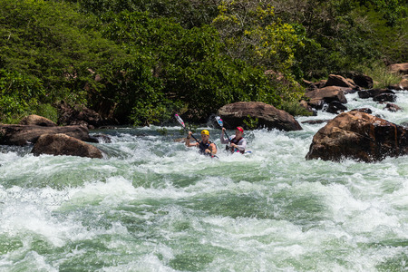 enviromnment: Dusi canoe race action drama at Inanda Rapids with paddlers going through rushing river waters