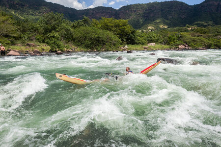 enviromnment: Paddlers break canoe around large river water rapid rock in dusi canoe race action drama at Inanda valley with teams going through dangerous rushing river waters