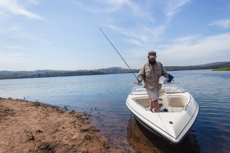 Fisherman getting off boat after morning fishing on dam waters  photo