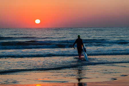 silhoutted: Surf-ski paddler silhouetted in training beach entry at dawn sun rising over ocean waters and sky