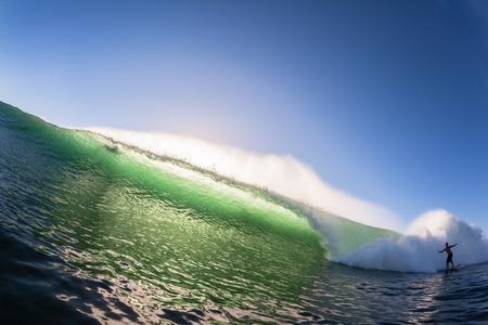 Wave Ocean sea wall of water crashing in color unidentified surfer Banco de Imagens - 26271309