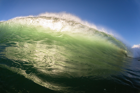 contrasts: Ocean wave swimming angle of upright vertical crashing wall of water energy beauty and power Stock Photo