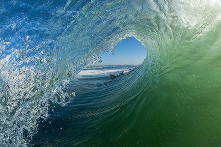 Oceaan golf zwemmen surfer metrorit hoek van opstaande verticale crashen muur van water energie schoonheid en kracht Stockfoto